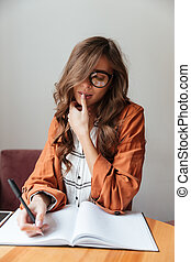 Portrait of an attractive woman taking notes