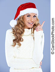 Portrait of an attractive woman wearing a red Santa hat