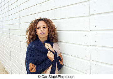 Portrait of an attractive young woman posing outdoors with sweater