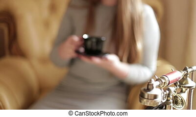 Portrait of an attractive young woman sitting on the couch in the living room family home , drinking fresh coffee , smiling . Well-being of life.