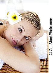 Portrait of an attractive young woman smiling at the camera in a spa having a back massage