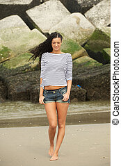 Portrait of an attractive  young woman walking on the beach