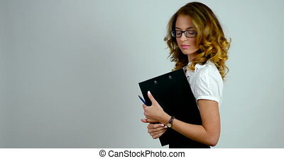 Portrait of an business woman stands in a studio and holds a black holder for paper
