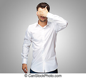 Portrait Of An Businessman Covering Eyes Isolated On Grey...