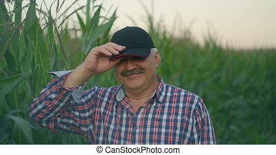 Portrait of an elderly farmer in a cornfield looking at the camera and smiling