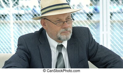 Portrait of an elderly man in hat, suit and glasses looking aside. 4K
