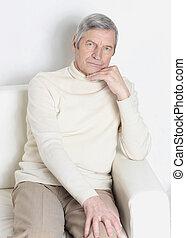 portrait of an elderly man sitting in a chair.