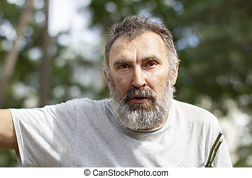 Portrait of an elderly man with a beard in the park.