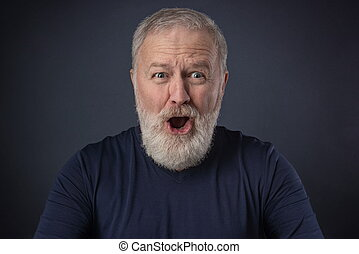 Portrait of an elderly man with a surprised mimic