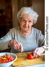 Portrait of an elderly woman chops vegetables for salad.