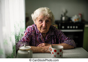 Portrait of an elderly woman sitting at the table.