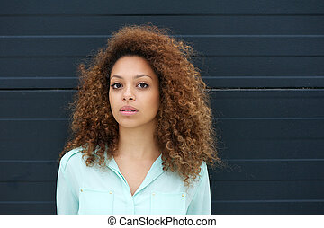 Portrait of an elegant young woman against black background