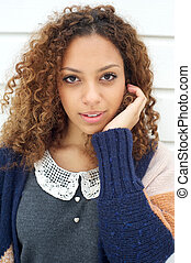 Portrait of an elegant young woman in sweater with hand in hair