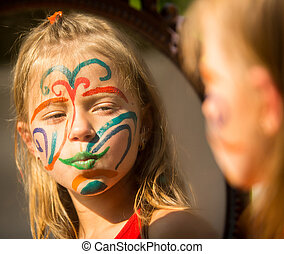 Portrait of an emotional little girl with paint on his face looks in the mirror.