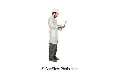 Portrait of an engineer in helmet using a laptop on white background.