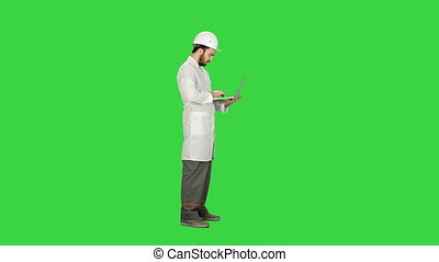 Portrait of an engineer in helmet using a laptop on a Green Screen, Chroma Key.