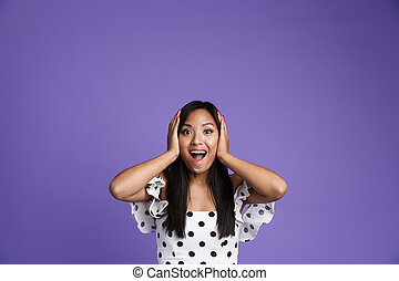 Portrait of an excited asian woman in dress