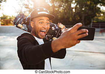 Portrait of an excited funny african male teenager in cap...