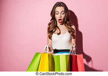 Portrait of an excited woman looking at colorful shopping bags