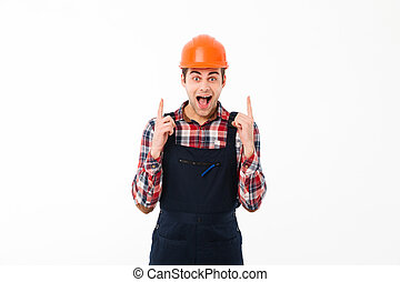 Portrait of an excited young male builder pointing