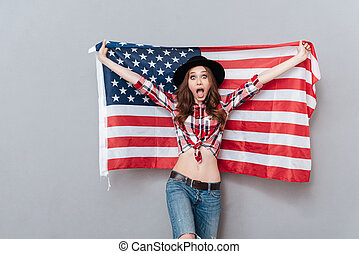 Portrait of an excited young woman holding USA flag