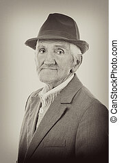Portrait of an expressive old man with hat