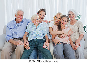 Portrait of an extended family sitting on couch and smiling...