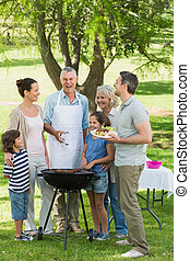 Portrait of an extended family standing at barbecue in the...
