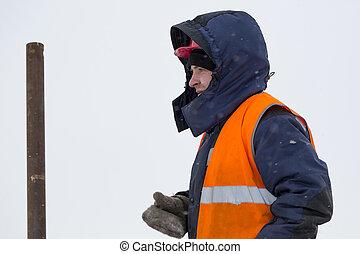 Portrait of an installer in a blue jacket and orange vest