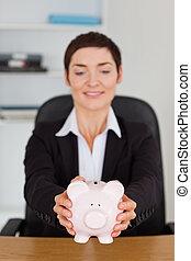 Portrait of an office worker holding a piggybank