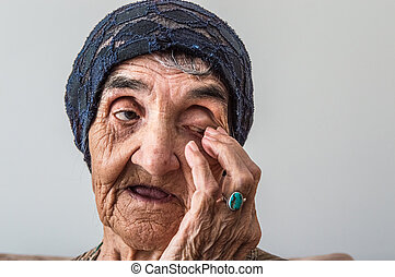 Portrait of an old grandma with a blue bonnet scratching her...