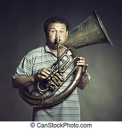 Portrait of an old man close up playing the trumpet. Studio photo