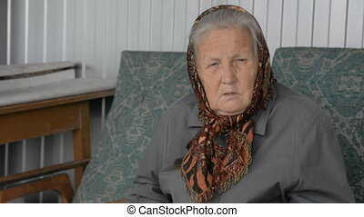 Portrait of an old woman in a brown kerchief sitting on a...