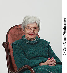 Portrait of an old woman sitting on a wooden rocking chair with fingers crossed, against a grey background.