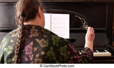 Portrait of an old woman with glasses near piano