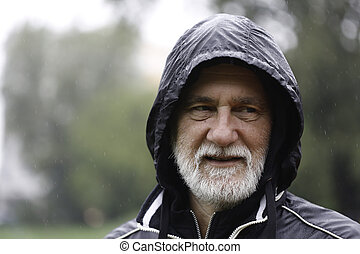 Portrait of an older white bearded man wearing a black hoodie on a rainy day with a blurry background