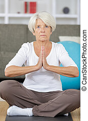 portrait of an older woman in sportswear exercising indoors