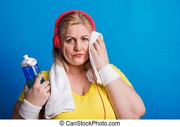 Portrait of an overweight woman in studio on a blue...