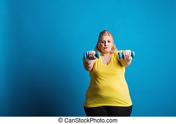 Portrait of an unhappy overweight woman with dumbbells in...