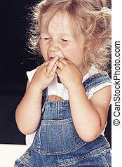 Portrait of an upset little girl in denim overalls, sitting in a studio on black background.