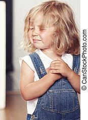 Portrait of an upset little girl in denim overalls, standing in studio.