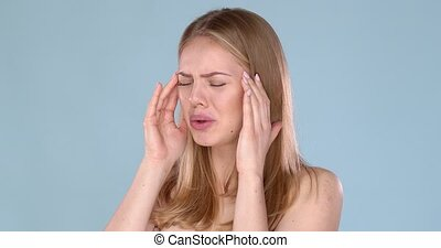 Portrait of an young woman with strong headache or migraine. Pain emotions on her face.