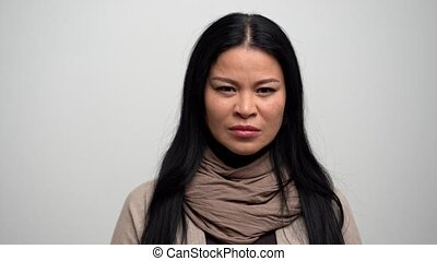 Portrait of angry Asian woman who breathes to calm down -...