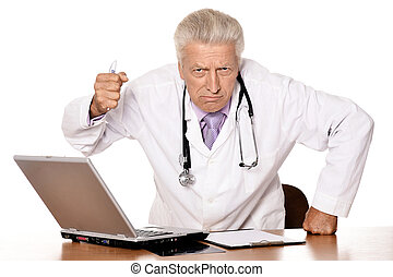 Portrait of angry doctor with a laptop on white background