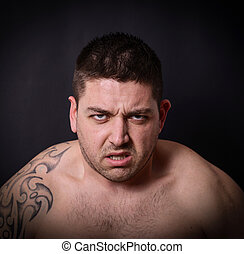 Portrait of angry man against dark background