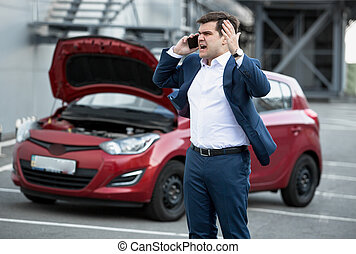 angry man talking by phone because of broke down car -...