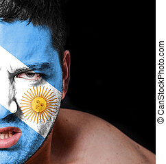 Portrait of angry man with painted flag of Argentina