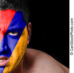 Portrait of angry man with painted flag of Armenia