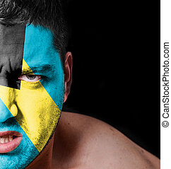 Portrait of angry man with painted flag of Bahamas