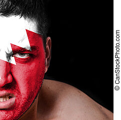 Portrait of angry man with painted flag of Bahrain